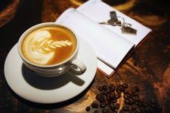 Tazza di caffè allo scrittorio e chiavi sul taccuino Fotografia Stock