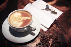 Tazza di caffè allo scrittorio e chiavi sul taccuino Fotografie Stock