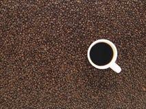 Tazza di caffè ambientale ed interi fagioli immagini stock libere da diritti