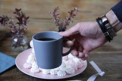 Tazza di caffè americano nella mano di un uomo sui precedenti della caramella gommosa e molle in piatto rosa e fiori della molla  immagine stock