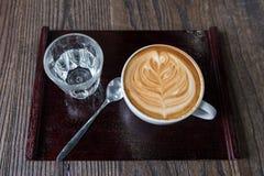 Tazza di caffè di arte del Latte con acqua potabile immagine stock libera da diritti