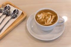 Tazza di caffè di arte del Latte con il cucchiaio fotografie stock