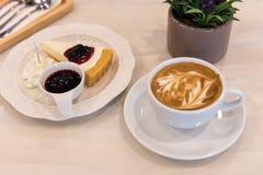 Tazza di caffè di arte del Latte con il dolce della torta immagine stock