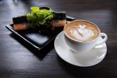 Tazza di caffè di arte del Latte con l'insalata del rotolo immagini stock