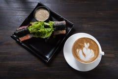 Tazza di caffè di arte del Latte con l'insalata del rotolo fotografie stock