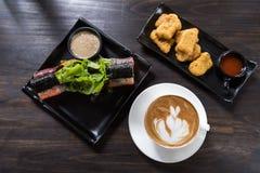 Tazza di caffè di arte del Latte con l'insalata del rotolo e la pepita di pollo fotografia stock libera da diritti
