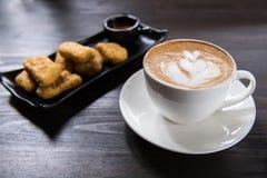 Tazza di caffè di arte del Latte con la pepita di pollo fotografia stock