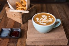 Tazza di caffè di arte del Latte con lo spuntino fotografie stock libere da diritti