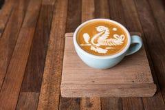 Tazza di caffè di arte del Latte sulla tavola di legno immagine stock
