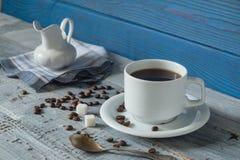 Tazza di caffè, beens e una brocca su un fondo dei bordi blu Fotografia Stock Libera da Diritti