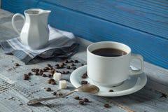 Tazza di caffè, beens e una brocca su un fondo dei bordi blu Immagini Stock