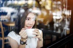 Tazza di caffè bianca bevente della ragazza dell'Asia in caffè Fotografie Stock Libere da Diritti