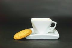 Tazza di caffè bianca con il biscotto su fondo scuro Immagini Stock