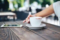 Tazza di caffè bianca con rossetto Sulla tavola un la tazza di caffè e un telefono fotografia stock