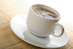 Tazza di caffè bianca sopra priorità bassa di bambù Fotografia Stock