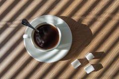 Tazza di caffè bianca sulla scrivania vicino alla finestra con i ciechi fotografia stock