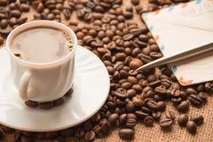 Tazza di caffè bianca; una lettera e una penna sui precedenti di cof Fotografia Stock