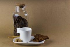 Tazza di caffè, biscotti e un barattolo di vetro in pieno dei chicchi di caffè Fotografia Stock Libera da Diritti