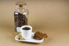 Tazza di caffè, biscotti e un barattolo di vetro in pieno dei chicchi di caffè Fotografie Stock Libere da Diritti