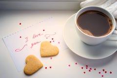 Tazza di caffè, biscotti sotto forma di un cuore e una dichiarazione Immagine Stock
