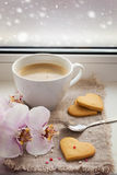 Tazza di caffè, biscotti sotto forma di un cuore ed orchidea sul BAC Fotografie Stock