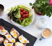 Tazza di caffè Bruschetta con l'uovo di quaglia e Parma fritti vista superiore della prima colazione soleggiata del pomodoro immagini stock libere da diritti