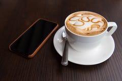 Tazza di caffè calda di arte del latte con lo Smart Phone fotografia stock libera da diritti