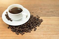 Tazza di caffè calda con i chicchi di caffè con lo spazio della copia sulla tavola di legno immagini stock libere da diritti