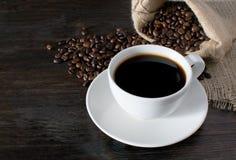 Tazza di caffè calda con i chicchi di caffè sulla tavola di legno fotografia stock libera da diritti