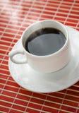 Tazza di caffè calda sulla stuoia rossa. Fine in su Immagine Stock Libera da Diritti