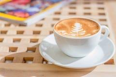 Tazza di caffè caldo con arte del latte e del libro sulla tavola di legno Immagini Stock