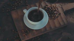 Tazza di caffè caldo con i semi di cacao torrefatti su fondo di legno rustico video d archivio