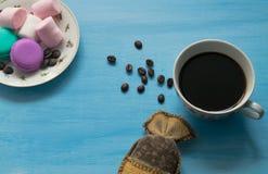 Tazza di caffè caldo con le caramelle gommosa e molle ed i maccheroni su fondo blu immagine stock libera da diritti