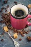 Tazza di caffè caldo con schiuma sui precedenti dei chicchi di caffè Fotografia Stock