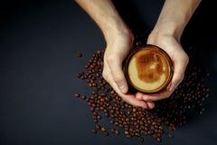 Tazza di caffè caldo nelle mani con i grani arrostiti sparsi sulla tavola fotografie stock