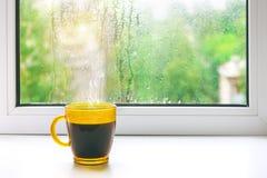 Tazza di caffè caldo sul davanzale Fuori della finestra la pioggia fotografia stock