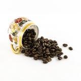 Tazza di caffè capovolta della porcellana con i chicchi di caffè isolati su bianco Fotografie Stock Libere da Diritti