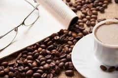 Tazza di caffè, chicchi di caffè, occhiali da sole e rivista bianchi Fotografia Stock