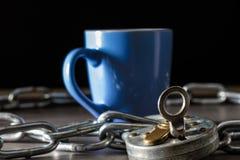 Tazza di caffè circondata da un briciolo a catena una serratura, concetto di dipendenza immagine stock libera da diritti