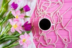 Tazza di caffè, collana bianca della perla e mazzo tenero di bei tulipani su fondo di legno rosa Fotografie Stock