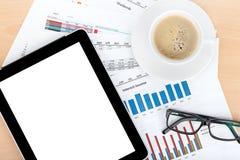 Tazza di caffè, compressa sopra le carte con i numeri e grafici Fotografia Stock