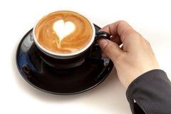 Tazza di caffè con arte del latte di forma del cuore sulla cima, mano che tiene la c Fotografie Stock