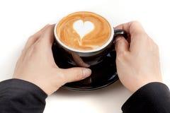 Tazza di caffè con arte del latte di forma del cuore sulla cima, mano che tiene la c Immagini Stock Libere da Diritti