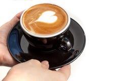 Tazza di caffè con arte del latte di forma del cuore sulla cima, servire delle mani Fotografie Stock Libere da Diritti
