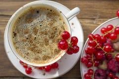 Tazza di caffè con cannella e le bacche fresche Fotografia Stock