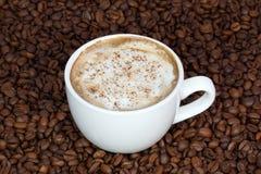 Tazza di caffè con cannella su un fondo dei chicchi di caffè fotografie stock