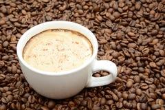 Tazza di caffè con cannella su un fondo dei chicchi di caffè fotografie stock libere da diritti