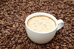 Tazza di caffè con cannella su un fondo dei chicchi di caffè immagine stock