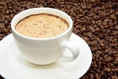 Tazza di caffè con cannella su un fondo dei chicchi di caffè fotografia stock libera da diritti