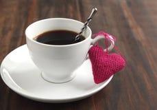 Tazza di caffè con cuore tricottato Fotografia Stock
